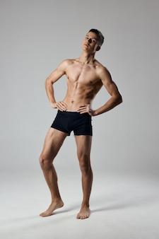 L'atleta sexy tiene le mani su una cintura in piena crescita su uno sfondo grigio bodybuilder fitness