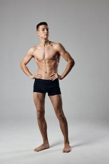 Atleta sexy tiene le mani su una cintura in piena crescita su un culturista grigio