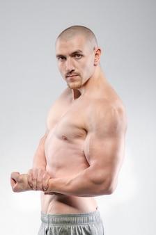 Atleta sexy in posa su uno sfondo bianco in topless. fitness.