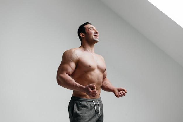Atleta sexy in posa su uno sfondo bianco in topless. fitness