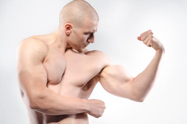Atleta sexy in posa su uno spazio bianco in topless. fitness.