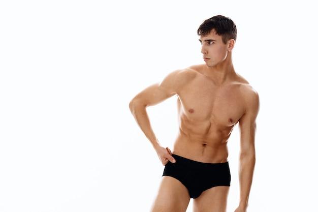 Uomo atletico sexy con addominali pompati in pantaloncini scuri sfondo isolato