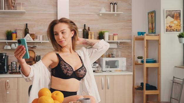 Donna bionda attraente sexy in reggiseno nero che tiene il telefono cellulare prendendo selfie durante la colazione godendo il tempo. seducente donna con tatuaggi utilizzando smartphone indossando biancheria intima temping al mattino.