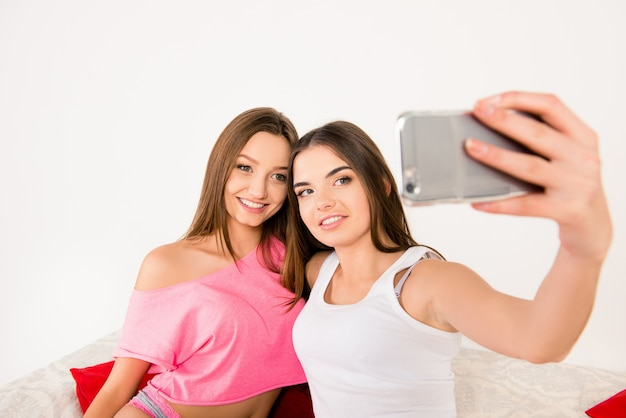 Ragazze attraenti sexy in pigiama che fanno selfie in camera da letto