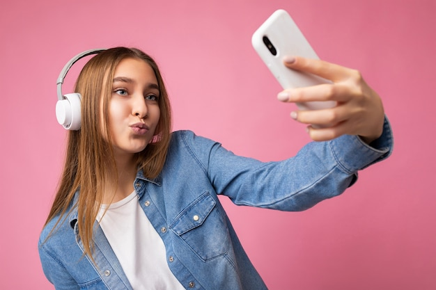 Giovane donna bionda sorridente felice attraente sexy che porta camicia alla moda del jeans blu e bianco casuale
