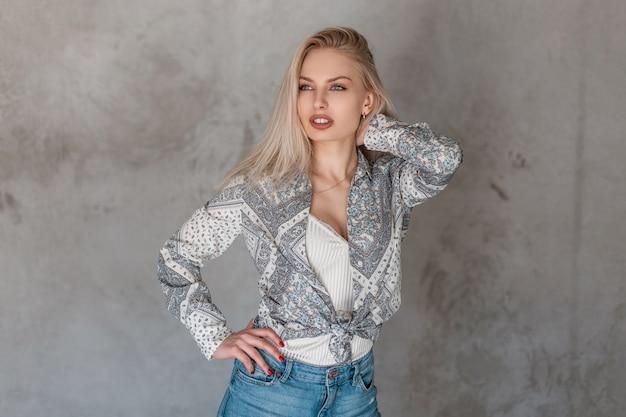 Giovane donna attraente sexy una bionda in una camicia alla moda con un motivo in una maglietta alla moda in jeans alla moda in studio vicino al muro grigio vintage
