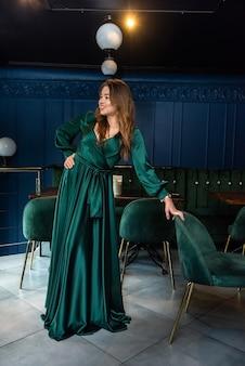 Giovane donna attraente sexy che porta vestito lungo verde che posa sulla sedia al caffè della città. eleganza