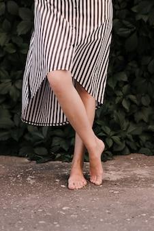 Piedi femminili a piedi nudi sexy. la donna sta sul marciapiede a piedi nudi