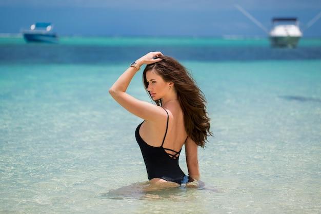 Donna sexy del modello della spiaggia divertendosi nuoto nell'oceano