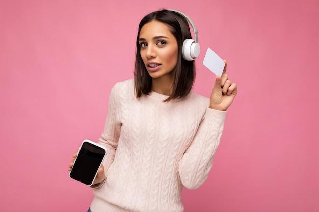 Bella donna castana adulta sexy che porta maglione casuale rosa isolato