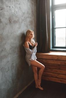 Bella bionda sexy in posa in lingerie nera e una camicia bianca.