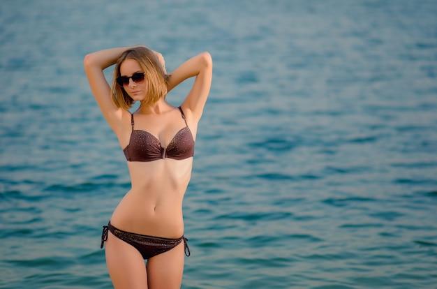 Sexy bella giovane donna caucasica in un bicchiere sulla spiaggia, è in piedi sull'acqua azzurra. ricreazione e coccole in riva al mare (oceano, fiume, lago) alla luce del tramonto.