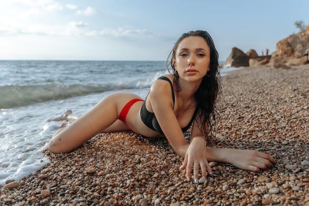 La bella ragazza sexy in costume da bagno è sdraiata sulla spiaggia