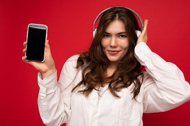 Bella giovane donna sorridente felice sexy che porta vestito casuale alla moda isolato sulla parete del fondo