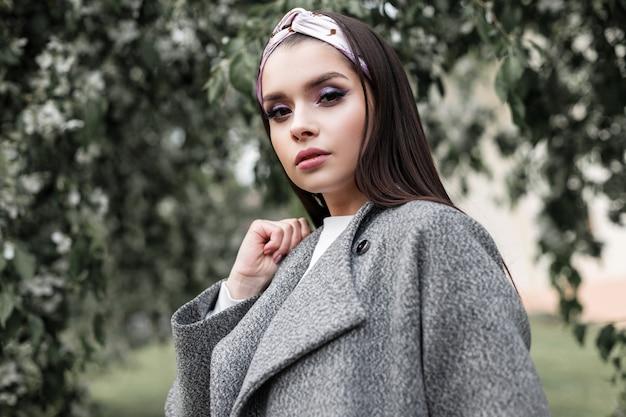 Bella giovane donna sexy in cappotto alla moda in bandana affascinante alla moda su priorità bassa di fogliame verde nel parco in primavera. la ragazza attraente in vestiti dalla nuova raccolta della gioventù posa all'aperto.
