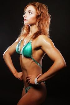 Donna sexy del bodybuilder bionda in bikini su superficie nera black