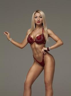Donna bionda sexy del culturista in bikini su fondo grigio