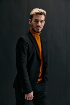 Ragazzo biondo sexy in vestiti scuri e maglione arancione ritagliata vista sullo sfondo nero