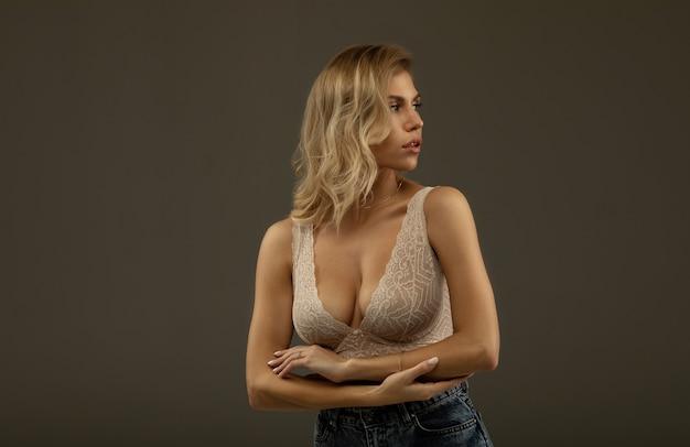 Ragazza bionda sexy con le labbra carnose in posa in biancheria intima e jeans.