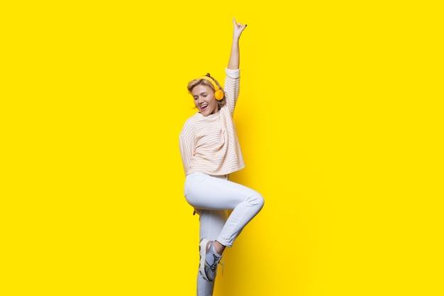 La signora bionda sexy sta sorridendo e ballando su una parete gialla dello studio che indossa le cuffie