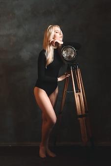 Donna bionda sexy in tuta a casa vicino a una lampada, torcia. figura perfetta, bel corpo.
