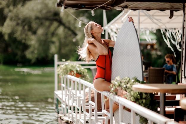 La donna bionda sexy si è vestita in costume da bagno rosso che si siede sull'inferriata del ristorante con un wakeboard che sta vicino all'acqua