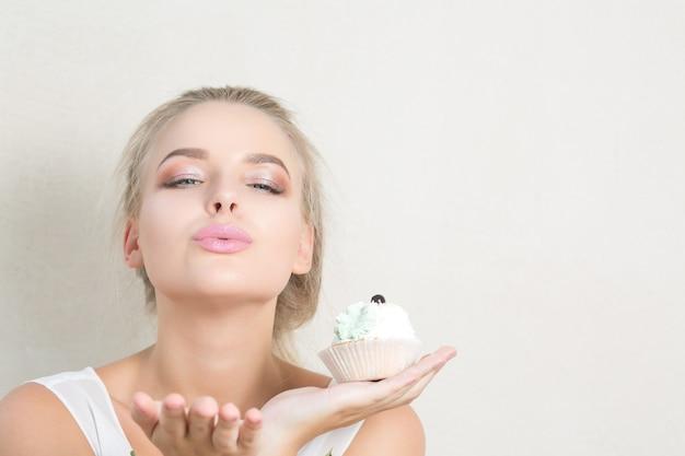 Donna bionda sexy che tiene un delizioso dessert con crema e invia un bacio d'aria. spazio per il testo