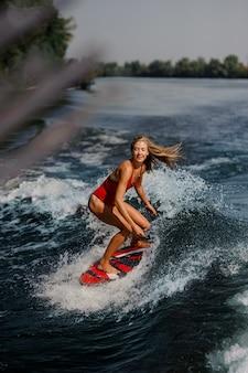 Donna bionda sexy che pratica il surfing a bordo giù l'acqua blu