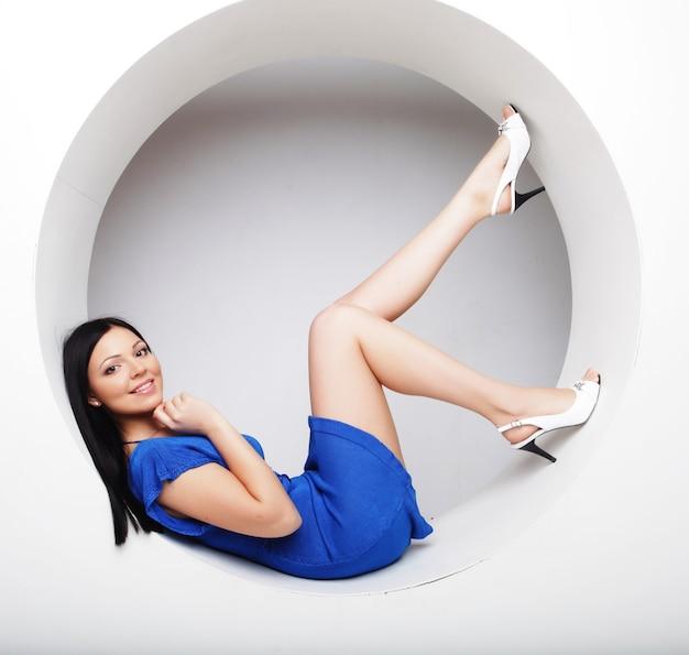Bruna sexy in abito blu seduta in cerchio