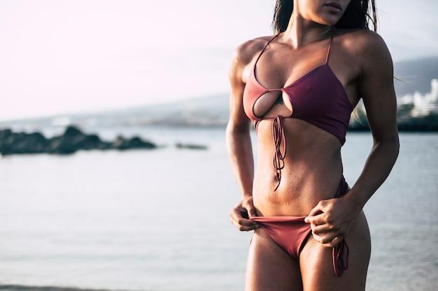 Parte del corpo del primo piano brunetta sexy in bikini rosso prendere il sole e posare come una modella che mostra il petto e la pancia piatta realizzati con fitness e allenamento e cibo sano. concetto sensuale per ragazza attraente