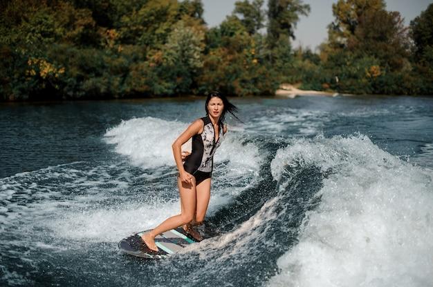 Ragazza sexy del brunette che guida sul wakeboard sul lago