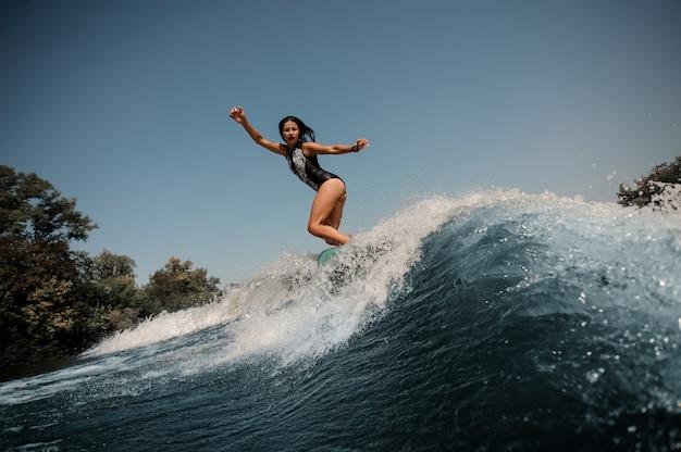 Ragazza sexy del brunette che guida sul wakeboard vicino al lago