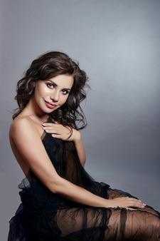 Bruna sexy con bei capelli ricci in un vestito nero chiaro