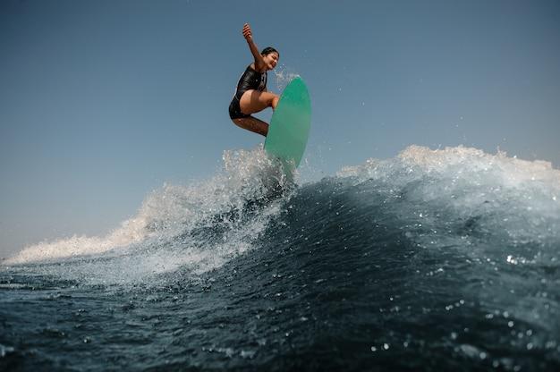 Donna sexy del brunette che salta su un wakeboard sull'alta onda blu
