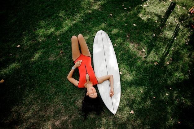 Donna sexy del brunette che si trova sull'erba verde con un wakeboard