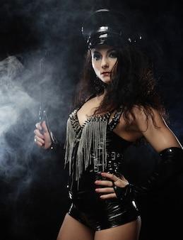 Padrona sexy della donna castana che tiene la frusta, sopra backgrouynd scuro con fumo, riprese in studio