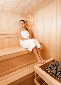 Donna castana sexy alla sauna che si siede con gli occhi chiusi