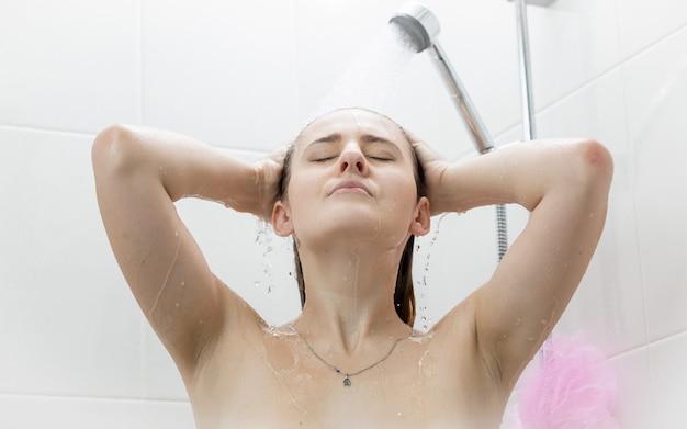 Donna bruna sexy che lava i capelli sotto la doccia