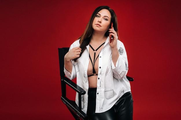 Donna sexy in fiamme in una camicia bianca seduta su una sedia con un telefono rosso su un muro rosso