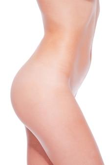 Glutei sexy. primo piano di giovane donna nuda in piedi su sfondo bianco