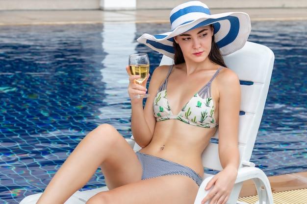 Donna caucasica sexy che indossa un bikini che si siede sulla spiaggia della sedia e che beve un cocktail vicino allo stagno.