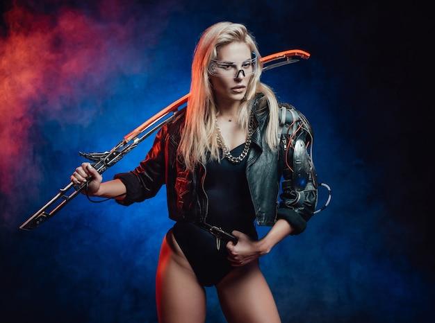 La donna sexy e affascinante con i capelli biondi in stile cyberpunk posa su sfondo blu scuro tenendo la lama incandescente sulla spalla.