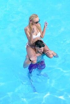 Coppia sexy che si rilassa nella piscina del resort e beve cocktail allegro giovane ragazzo e signora che riposa mentre piscina all'aperto coppia felice che si rilassa in piscina a ferro di cavallo baia bermuda