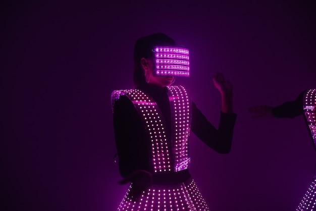 Ballerina sexy della discoteca che balla in un vestito uv alla musica. feste e balli.