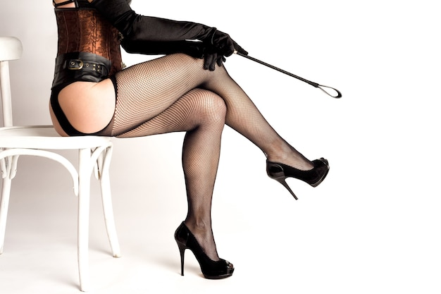 Donna dominatrice sexy in calze a rete che tiene frustino, isolato su priorità bassa bianca.