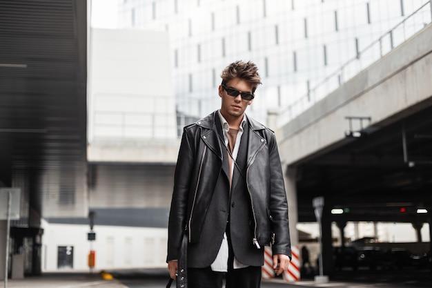 Giovane europeo sexy in occhiali da sole in giacca di pelle nera oversize di moda giovanile con un'acconciatura alla moda sta riposando vicino a un edificio moderno della città in una giornata di primavera. hipster ragazzo serio all'aperto