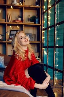 Donna bionda di modo sexy con il maglione rosso che si siede sul letto e sui sorrisi