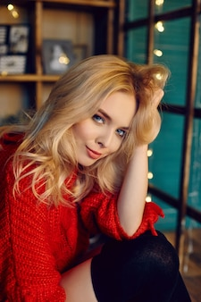 Donna bionda di modo sexy con il maglione rosso