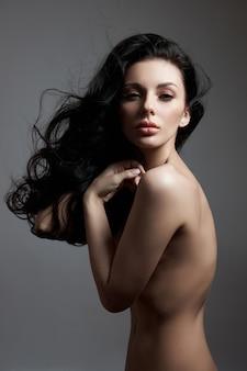 Moda sexy donna nuda con i capelli lunghi, i capelli ricci forti di una ragazza bruna.