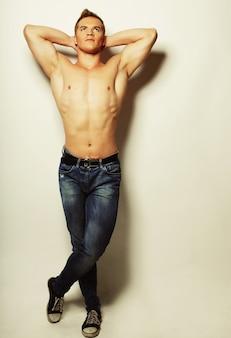 Ritratto di moda sexy di un modello maschio caldo in jeans alla moda con la posa del corpo muscoloso